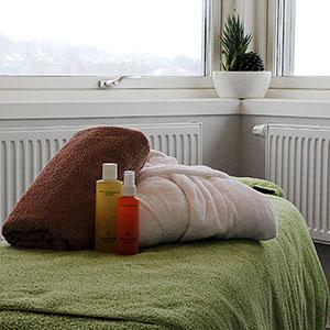 Handduk, badrock och massageolja står på massagebänk