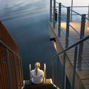 Tjej sitter längst ner på trappan till vattnet
