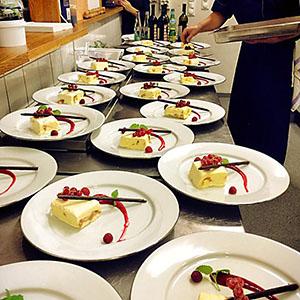 Kock lägger upp dessert på tallrikar