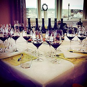 Ett flertal vinglas fyllda med rödvin står på ett bord
